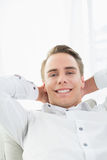 Smiling relaxed young man lying on sofa Stock Photos