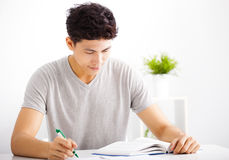 Smiling relaxed young man reading  book Royalty Free Stock Photos