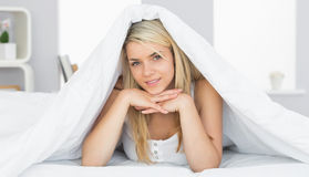 Smiling relaxed young woman lying in bed Royalty Free Stock Images