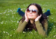 Smiling relaxing girl. Smiling dreaming young woman with head in hands relaxing, laying in green grass with daisy flowers. Prague, Czech Republic Stock Photography
