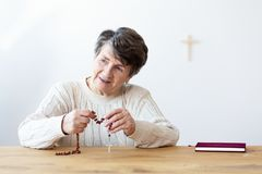 Smiling religious grandmother with rosary stock photos