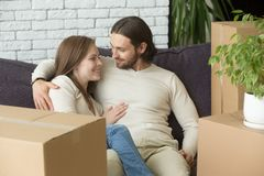 Smiling renters hugging on couch in new home with boxes. Happy loving couple tenants embracing on couch in living room on moving day, young smiling family Stock Photos