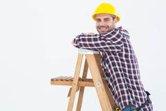 Smiling repairman climbing ladder Royalty Free Stock Photos