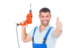 Smiling repairman with drill machine gesturing thumbs up Stock Photography