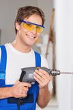 Smiling repairman with drill Royalty Free Stock Images