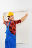 Smiling repairman gluing wallpaper Stock Photography
