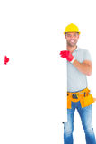 Smiling repairman holding blank billboard Royalty Free Stock Image
