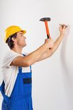 Smiling repairman nailing Stock Photo