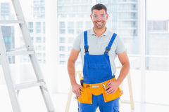 Smiling repairman in overalls at bright office. Portrait of smiling repairman in overalls standing hands on hips at bright office Royalty Free Stock Photo