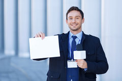 Smiling reporter with microphone holds a sheet of Stock Photography