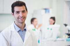 Smiling researcher with colleagues in background at lab stock photo