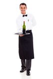 Sommelier with wine. Smiling restaurant sommelier holding tray of wine and glass stock photography