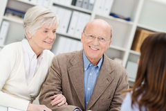 Smiling retired couple in a business meeting. Getting advice from their insurance broker or financial adviser as they sit in her office Royalty Free Stock Photo