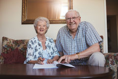 Smiling retired couple looking over documents. Portrait of a smiling retired couple looking over documents. Senior caucasian men and women sitting on sofa at old stock images