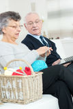 Smiling retired couple relaxing at home on sofa Stock Image