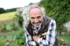 Smiling retired man standing in garden Stock Image
