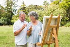 Smiling retired woman painting on canvas with husband Stock Images