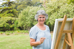 Smiling retired woman painting on canvas Royalty Free Stock Photo