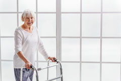 Smiling retiree holding gutter frame in hand Stock Images