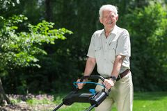 Smiling retiree with lawn mower Stock Image