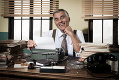Smiling retro reporter working at office desk Stock Photo