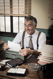 Smiling retro reporter working at office desk Royalty Free Stock Image