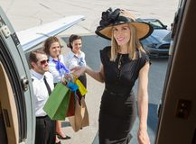 Smiling Rich Woman With Shopping Bags Boarding. Portrait of smiling rich women with shopping bags boarding private jet while pilot and airhostess looking at her Royalty Free Stock Images