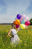 Smiling Rockabilly Girl with colorful balloons on the meadow Stock Photography