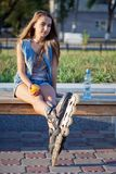 Smiling roller girl sitting on the bench Royalty Free Stock Photo