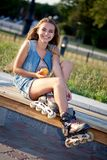 Smiling roller girl sitting on the bench Royalty Free Stock Photography