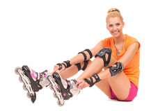 Smiling roller girl sitting on the floor. Stock Photos