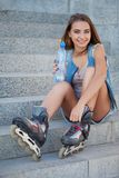 Smiling roller girl sitting on the stairs Royalty Free Stock Images