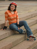 Smiling Rollerskating Girl. Sitting on Stair Steps Royalty Free Stock Photos