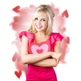Smiling romantic blond female hugging love heart Stock Images