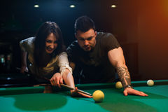 Smiling romantic couple playing snooker in club Stock Photography