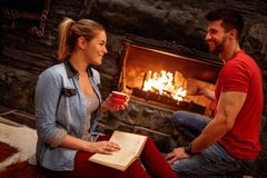 Smiling couple relaxing at home front of fireplace Royalty Free Stock Photos