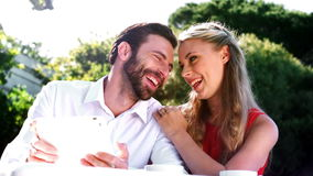 Smiling romantic couple using digital tablet stock footage