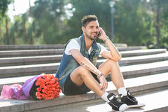 Smiling romantig guy speaking on the phone, bouquet of roses Royalty Free Stock Photo