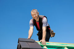 Smiling roofer on top of the roof Royalty Free Stock Photo