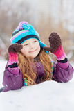 Smiling rosy girl  lies on snowdrift Royalty Free Stock Images