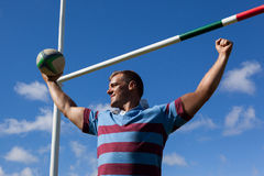 Smiling rugby player holding ball with arms raised against blue sky. Low angle view of smiling rugby player holding ball with arms raised by goal post against Stock Photos