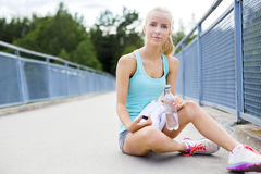 Smiling runner sitting on the ground and takes a break Stock Photo