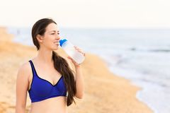 Woman drinks water on the sea beach royalty free stock photo