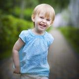 Smiling running toddler girl in motion. Portrait of a smiling running toddler girl in motion outdoors Stock Photo
