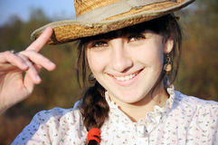 Smiling rural girl with straw hat. Outside Royalty Free Stock Photography