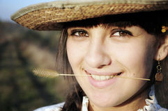 Smiling rural girl with straw hat. And a straw between her teeth Royalty Free Stock Photography
