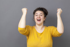 Smiling 20s big woman expressing fun victory Royalty Free Stock Image