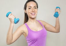 Smiling 20s brunette girl exercising with dumb bells for toned arms and wellness Royalty Free Stock Photos