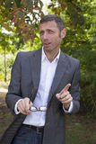 Smiling 40s businessman acting cool for lunch break in park Royalty Free Stock Photos