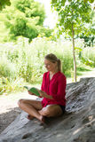 Smiling 20s girl reading a summer book under a tree. Outdoors reading - beautiful young suntanned blond woman reading on a giant stone in the shade for Royalty Free Stock Photography